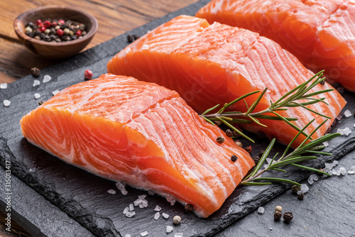 Leinwand Poster Fresh salmon fillets on black cutting board with herbs and spices