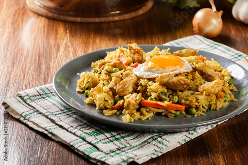Fototapeta Fried rice nasi goreng with chicken egg and vegetables on a plate. obraz