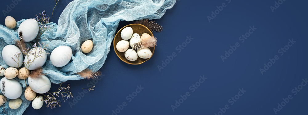 Fototapeta Easter banner with painted eggs and napkin on dark blue backround. Top view, flat lay with copy space.