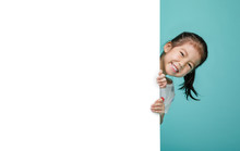 Smiling Happy Cute Child Hiding Behind A Blank White Board, Empty Space In Studio Shot Isolated On Colorful Blue Background