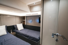 Luxury Yacht Interior: Large Sleeping Cabins For Two Passengers. Bed Pillows Porthole And Tv.