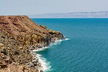 Jordan. Dead Sea. Dead Sea Coastline In Jordan. Cliffs Descend Into Emerald Water Of Dead Sea. Closeup Of Salt Crystals Along Coast. Waves Splash To Rocks Covered With Crystals Of Salt.