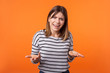 canvas print picture - What do you want? Portrait of confused annoyed woman with brown hair in long sleeve shirt raising arms, asking and having no idea what happening. indoor studio shot isolated on orange background