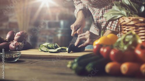 Obraz na plátně Woman slicing fresh vegetables and preparing a healthy meal