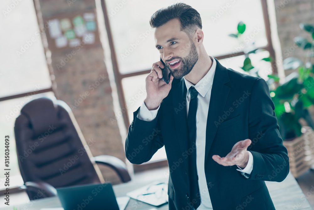 Fototapeta Photo of successful handsome business guy holding telephone speaking partners friendly mood wear black blazer shirt tie suit standing near table office indoors