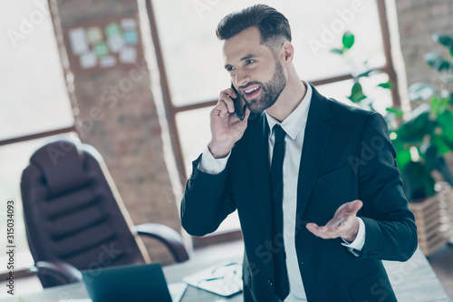 Obraz Photo of successful handsome business guy holding telephone speaking partners friendly mood wear black blazer shirt tie suit standing near table office indoors - fototapety do salonu