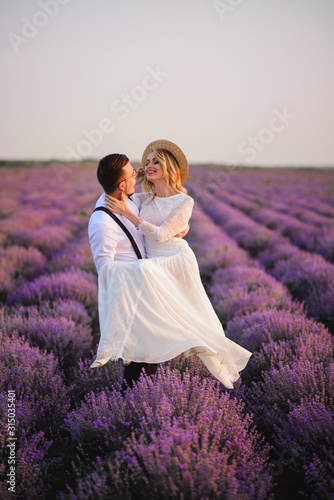 Fototapeta Happy groom holding his bride in his arms in blooming lavender field at sunset obraz