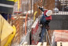 Male Construction Worker Installing Concrete Retaining Wall Rebar On Construction Site