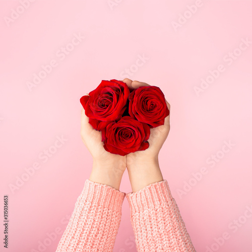 Three red roses forming a heart in female palms Wallpaper Mural