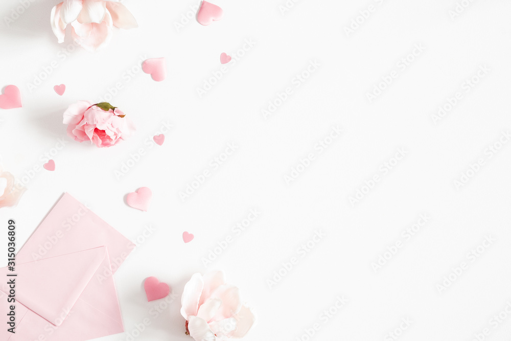 Fototapeta Valentine's Day background. Pink flowers, envelope, hearts on white background. Valentines day concept. Flat lay, top view, copy space
