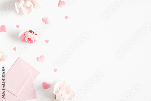 Fototapeta Valentine's Day background. Pink flowers, envelope, hearts on white background. Valentines day concept. Flat lay, top view, copy space obraz