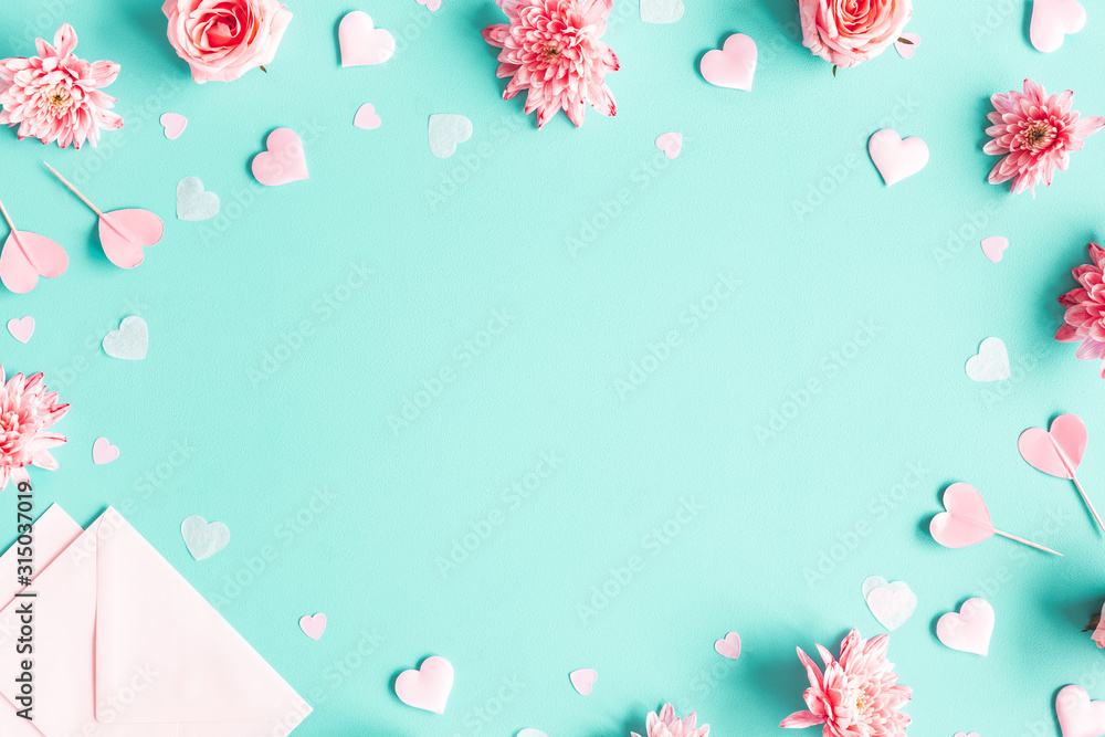 Fototapeta Valentine's Day background. Pink flowers, envelope, hearts on pastel blue background. Valentines day concept. Flat lay, top view, copy space