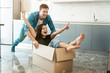 young couple husband and wife looking happy having fun while unpacking and moving in new appartment. husband carrying his wife in box on the floor