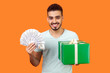 canvas print picture - Cashback and credit for shopping. Portrait of cheerful buyer, man with beard in white t-shirt holding gift box and lots of money, smiling at camera. indoor studio shot isolated on orange background