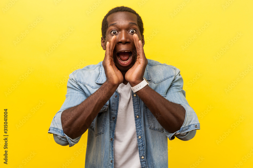 Fototapeta Attention! Portrait of scared man in denim shirt holding hands near wide open mouth and shouting announcement, looking with big eyes, shocked frightened face. studio shot isolated on yellow background