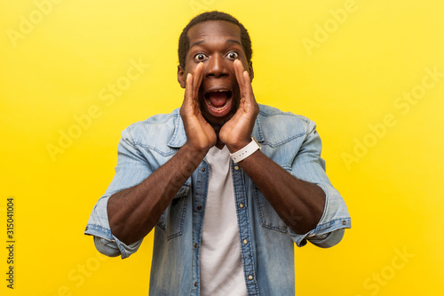 Photo Attention! Portrait of scared man in denim shirt holding hands near wide open mouth and shouting announcement, looking with big eyes, shocked frightened face