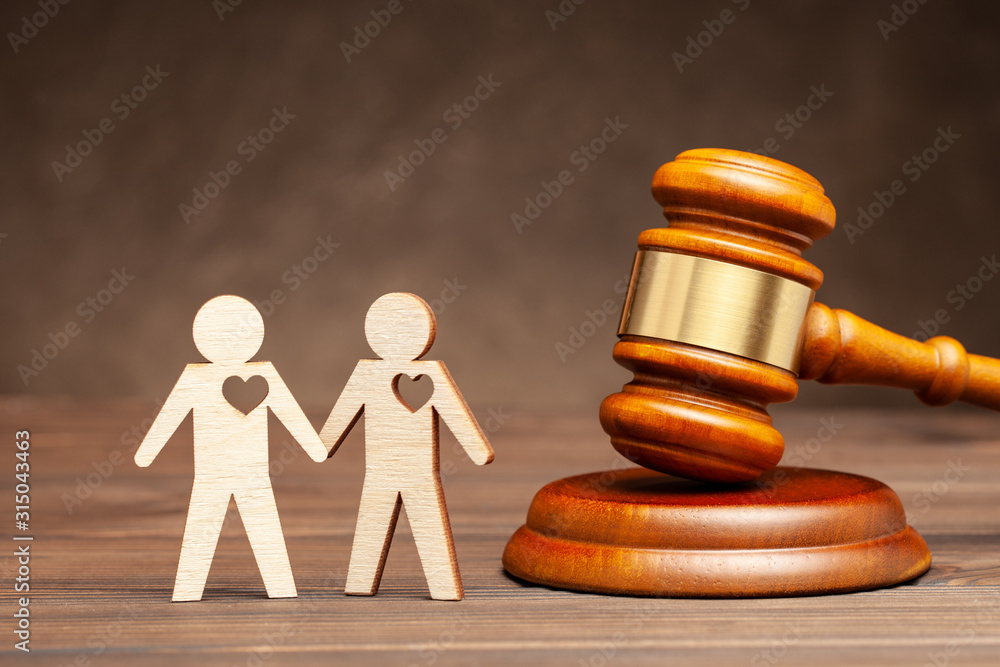 Fototapeta Legalize gay marriage. Two gay men holding hands against the background of a judge's hammer. Law and marriage of same-sex people.