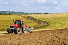 Farmer In Red Tractor Preparin...