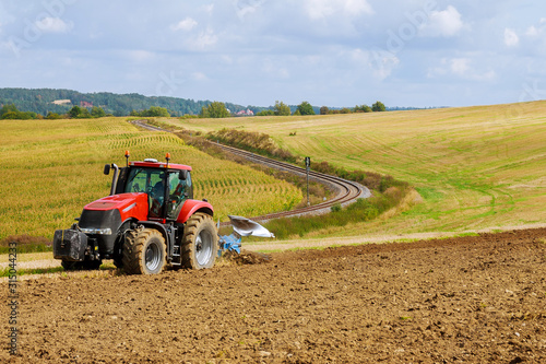 Farmer in red tractor preparing land with plow for sowing Canvas Print