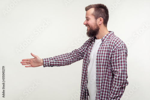 Side view of friendly bearded man in casual plaid shirt reaching out hand to handshake, getting acquainted at job interview, meeting new people Canvas Print