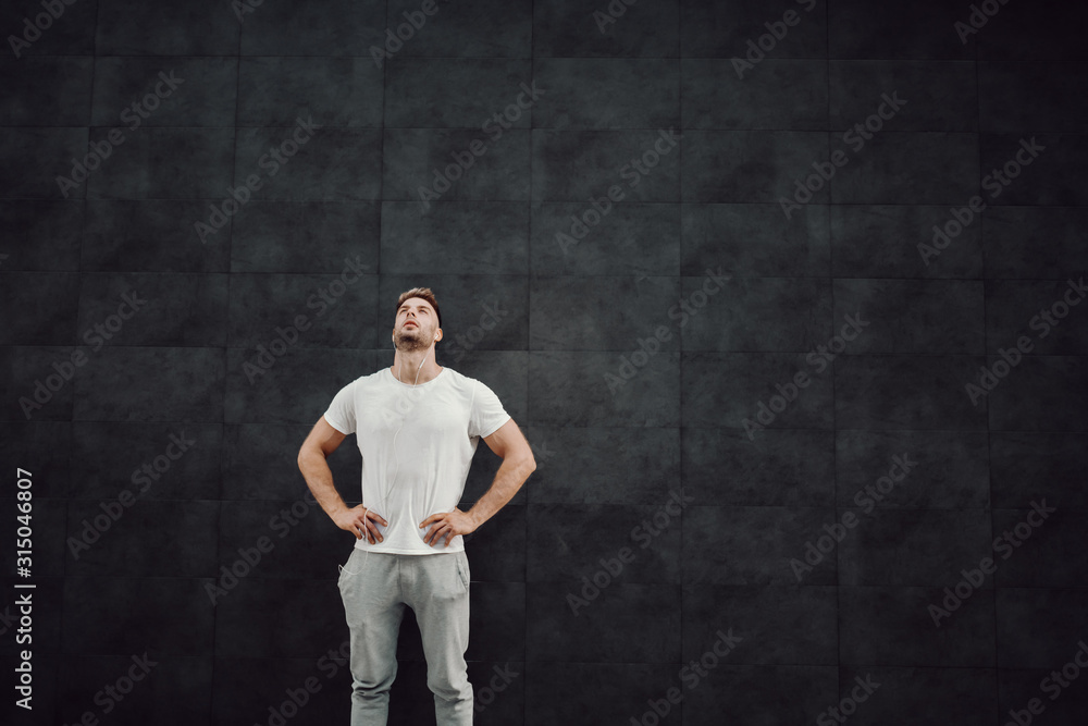 Obraz Attractive fit caucasian sportsman in tracksuit and in t-shirt standing in front of gray wall with hands on hips and resting. In ears are earphones. fototapeta, plakat