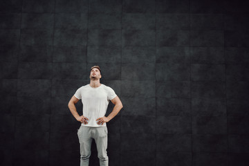 Attractive fit caucasian sportsman in tracksuit and in t-shirt standing in front of gray wall with hands on hips and resting. In ears are earphones.