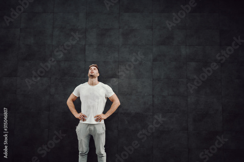 Fototapeta Attractive fit caucasian sportsman in tracksuit and in t-shirt standing in front of gray wall with hands on hips and resting. In ears are earphones. obraz