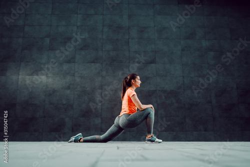 Fototapeta Side view of attractive caucasian sportswoman in shape dressed in sportswear and with ponytail stretching leg