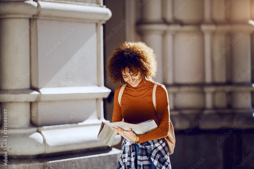 Fototapeta Beautiful young mixed race female tourist with curly hair and bag on back standing in front of old building and looking at map.