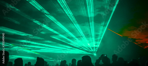 Obraz  colorful outdoor laser show with silhouette of people - fototapety do salonu