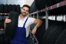 Male Mechanic With Car Tire In...