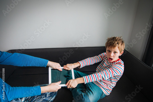 Obraz computer addiction- father taking touch pad from angry child - fototapety do salonu