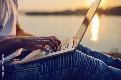 Cropped picture of Caucasian man sitting in nature and using laptop. In background is river and sunset. Selective focus on hands. - 315051461