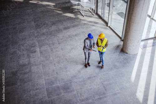 Obraz Top view of architect holding tablet and talking with construction worker about new ideas on project they working on. Building in construction process interior. - fototapety do salonu