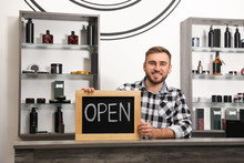 Young Business Owner Holding OPEN Sign In His Barber Shop