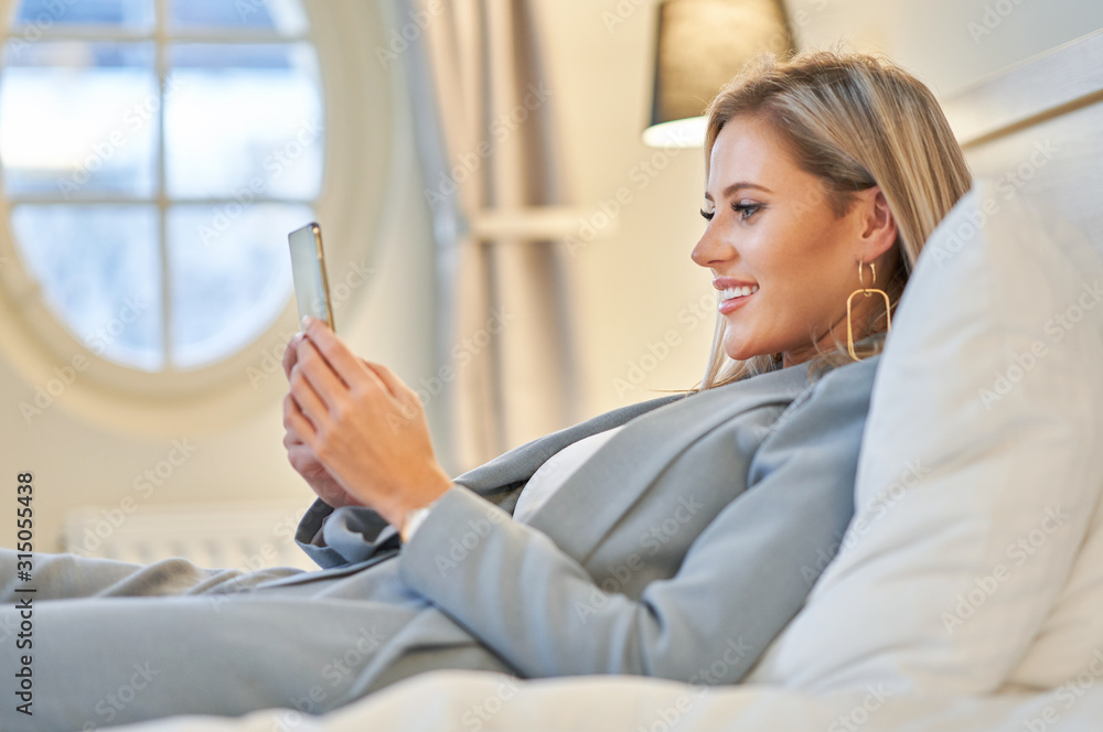 Fototapeta Businesswoman using tablet computer in hotel room