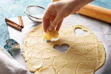 Cookie Dough Hearts In Hand On Blue Background With Rolling Pin, Strainer And Cinnamon
