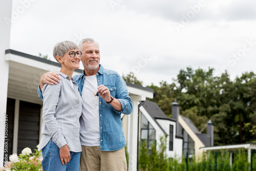 mature man holding keys of new house and hugging smiling woman