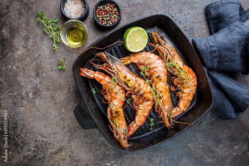 Fotografia Grilled giant tiger prawns in frying pan with lemon and spices on vintage dark background, top view, copy space