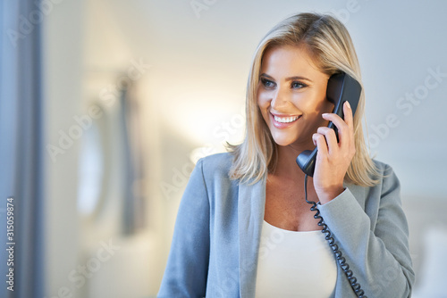 Businesswoman talking on the phone in hotel room Wallpaper Mural