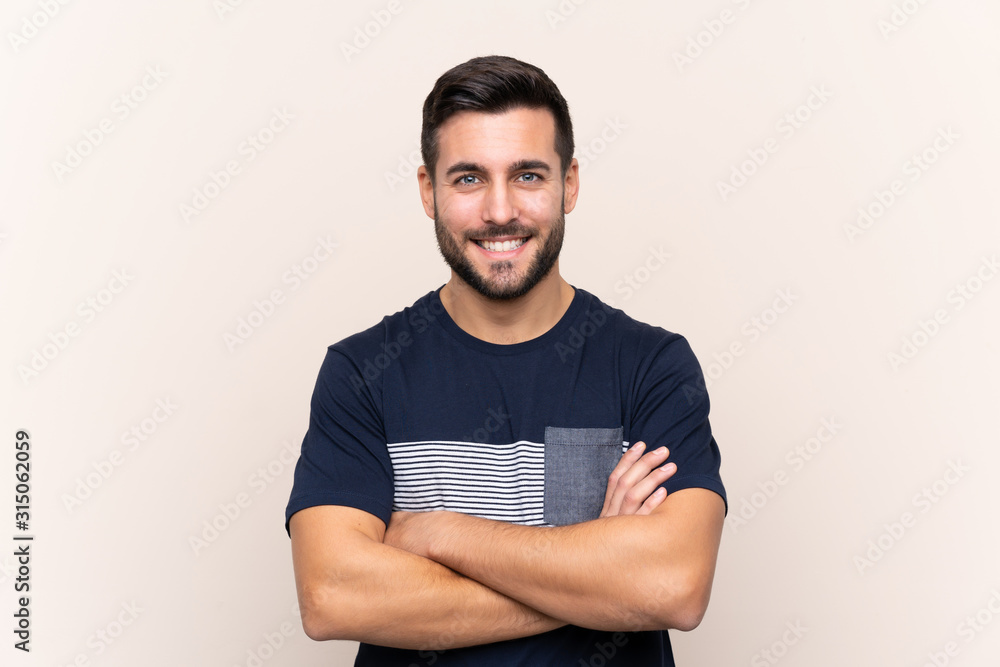 Fototapeta Young handsome man with beard over isolated background keeping the arms crossed in frontal position