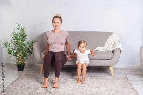 Young pretty woman and her cute daughter squatting leaning hands around on sofa, happy family doing gymnastics exercise together at home, fitness training with child. body care, healthy lifestyle