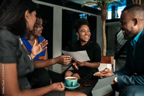 All african casual business meeting. Candid real happy moment between four work colleagues. - fototapety na wymiar