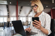 Photo of pleased blonde woman using cellphone and laptop while sitting