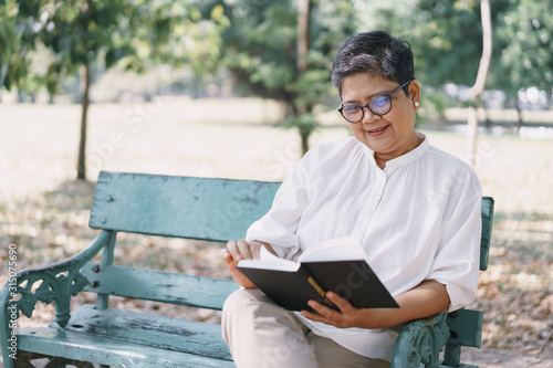 Tablou Canvas Happy elderly asian woman while sitting reading  book on the bench in the park