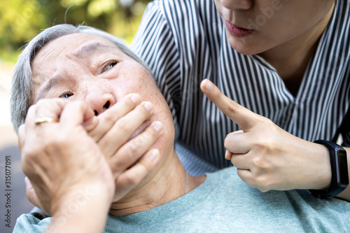 Angry asian woman covering senior mouth and showing silence gesture, keep a secr Canvas Print