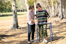 Asian Senior Woman Use Walking Aid During Rehabilitation After Knee Surgery, Young Carer Assisting Reassuring Mature Elderly People Practice Walking With Walker,female Caregiver Help,care,support