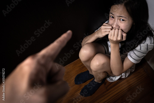 Sad asian child girl sit on floor,feel fear,pain,cry, stop physical abuse and domestic violence, angry man or father scolds frightened daughter,campaign against violence and aggression concept Fototapeta