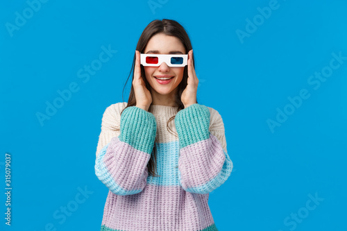 Obraz Turn on, lets start. Attractive amused and happy smiling young woman in winter sweater, wear 3d glasses and grinning, tempt see new premiere in cinema, watching movie over blue background - fototapety do salonu