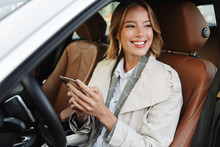 Image Of Beautiful Businesslike Woman Sitting In Car And Using Cellphone